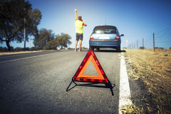 Emergency triangle on the road. Stopped car and man calling by phone in the background Stock Photos