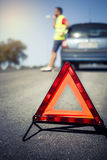 Emergency triangle on the road. Stopped car and man calling by phone in the background Stock Photography
