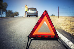 Emergency triangle on the road. Stopped car and man calling by phone in the background Royalty Free Stock Images