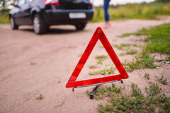 Emergency triangle stop sign on the road. Stopped car a in the background Royalty Free Stock Photos