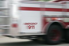 Emergency vehicle. Moving firetruck with Emergency Call 911 slogan visible Stock Photos