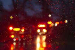 Emergency Vehicles Flashing Through a Wet Windshield Darkly Royalty Free Stock Photography