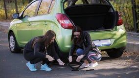emergenza Due donne al bordo della strada che prova a cambiare una gomma dalla vostra automobile con un Jack stock footage