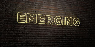 EMERGING -Realistic Neon Sign on Brick Wall background - 3D rendered royalty free stock image Royalty Free Stock Photography