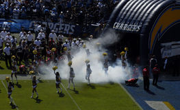 Emerging from the tunnel. Cheerleaders and players emerge through a smokey tunnel during a game at Qualcomm Stadium in San Diego royalty free stock photos