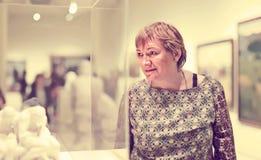 Emeryt kobiety dopatrywanie przy rzeźbą zdjęcie stock