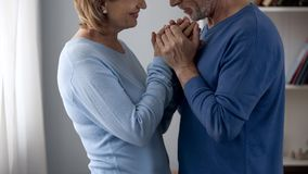 Emeryt pary mienia ręki, patrzeje each inny z miłością i gratefulness zdjęcie stock