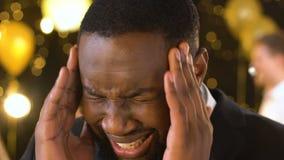 Emicrania di sofferenza dell'uomo afroamericano estremamente infelice al partito, tempie di lucidatura archivi video