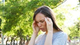 Emicrania di sofferenza della donna adulta in un parco video d archivio