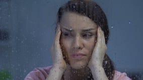 Emicrania di sofferenza della donna, tempie di lucidatura vicino alla finestra piovosa, sensibilità del tempo stock footage