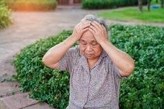 Emicrania paziente asiatica della donna senior o anziana della signora anziana mentre sedendosi sul letto nel reparto di ospedale immagini stock
