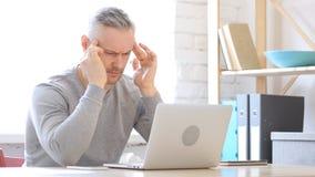 Emicrania, uomo Medio Evo di tempo che lavora al computer portatile Immagini Stock Libere da Diritti