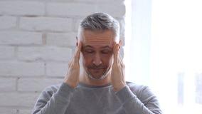 Emicrania, uomo Medio Evo lavorante frustrato in ufficio Immagine Stock