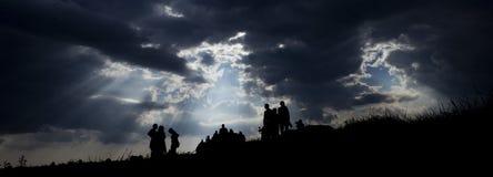 Emigrants on the way. Sun rays illuminate people. Immigration of people emigration sky clouds sun stock photo