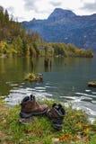 Emigrar botas cerca del lago en día soleado imagen de archivo