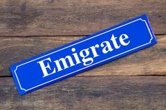 Emigrate street sign on wooden background. As symbol royalty free stock photography