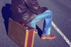 Emigration, resettlement, refugee, migration. The man in jeans with a suitcase.Photo toned in retro style royalty free stock photo