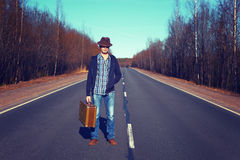 Emigration, resettlement, refugee, migration. The man in jeans with a suitcase.Photo toned in retro style royalty free stock image
