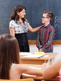 Eminent boy at chalkboard. Teacher praise eminent math boy at chalkboard, in front of the whole class Stock Image