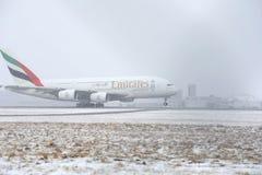 Emirat-Fluglinien A380, die von der schneebedeckten Rollbahn sich entfernen Lizenzfreie Stockfotografie