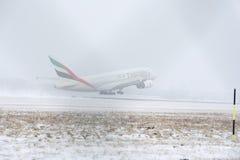 Emirat-Fluglinien A380, die von der schneebedeckten Rollbahn sich entfernen Lizenzfreies Stockfoto
