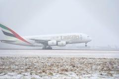 Emirat-Fluglinien A380, die von der schneebedeckten Rollbahn sich entfernen Stockbilder