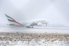 Emirat-Fluglinien A380, die von der schneebedeckten Rollbahn sich entfernen Stockfotos