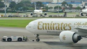 Emirater Boeing 777-300ER som tillbaka skjuts på den Changi flygplatsen Arkivfoton