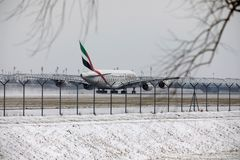 Emirates Airbus A380-800 A6-EEB, Munich Airport MUC. Emirates Airbus A380-800 A6-EEB doing taxi in Munich Airport MUC, winter time with snow on runway Royalty Free Stock Photo
