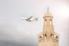 Emirates aircraft is taking off from DXB airport near mosque Royalty Free Stock Image