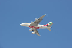Emirates Airline flying on Bright Blue Sky Royalty Free Stock Photography