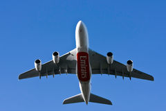 Emirates airlines Airbus A380 airliner flying low. Emirates Airlines giant Airbus A380 airliner flying low overhead against blue sky Stock Image