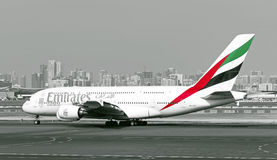 Emirates Airlines Airbus A380 aircraft. Emirates Airlines Airbus A380 super jumbo aircraft on the Dubai International Airport (DXB) runway. Dubai city skyline in Royalty Free Stock Photography