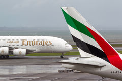 Emirates Airlines Airbus A380 aircraft taxis past the tail of Emirates airlines Boeing 777 aircraft. Stock Photography