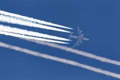 Emirates airlines Airbus A380 flying at high altitude with a large contrail forming behind it. royalty free stock photography