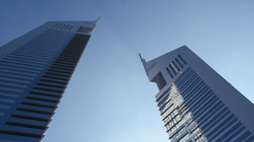Emirates Towers. The Emirates Towers, Dubai's first high rise buildings. The taller tower on the left is reflected in the blue windows of the right tower stock photo