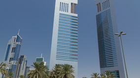 Emirates Twin Towers, Dubai, timelapse. Emirates Twin Towers at the day time with palms, Dubai. One tower is 1165 feet high and the other is 1014 feet high stock footage