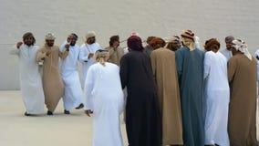 Emirati-M?nner, die das Yowla, einen traditionellen Tanz im Erbe Arabische Emirates nahe bei einem historischen Geb?ude durchf?hr stock video