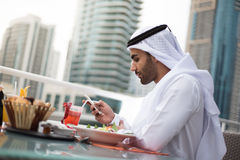 Emirati Man Using Mobile Phone in a Restaurant Stock Images