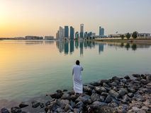 Emirati man wearing traditional cloth on the beach looking at Abu Dhabi city famous landmark at towers at sunset.  royalty free stock photos