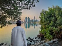 Emirati man wearing traditional cloth on the beach looking at Abu Dhabi city famous landmark at towers at sunset.  stock image