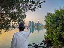 Emirati man wearing traditional cloth on the beach looking at Abu Dhabi city famous landmark at towers at sunset.  royalty free stock image