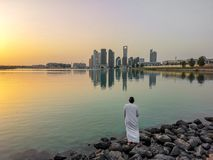 Emirati man wearing traditional cloth on the beach looking at Abu Dhabi city famous skyline at sunset royalty free stock photography