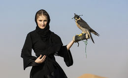Emirati woman with a falcon. Emirati woman in traditional emirati dress (abaya) with a falcon Royalty Free Stock Image