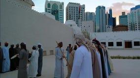 Emiratimensen die Yowla, een traditionele dans in de erfenis van de Verenigde Arabische Emiraten naast een historisch gebouw uitv stock video