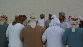 Emiratimensen die Yowla, een traditionele dans in de erfenis van de Verenigde Arabische Emiraten naast een historisch gebouw uitv stock footage