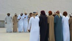 Emiratimensen die Yowla, een traditionele dans in de erfenis van de Verenigde Arabische Emiraten naast een historisch gebouw uitv stock videobeelden