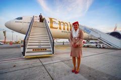 Emiratmannschaftsmitglied nahe Flugzeugen Stockfotos