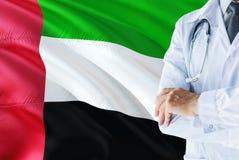 Emirian Fabrykuje pozycję z stetoskopem na Zjednoczone Emiraty Arabskie flagi tle Krajowy system opieki zdrowotnej pojęcie, medyc obraz royalty free