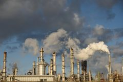 Emisiones que suben de la pila de humo de una refinería industrial del petróleo y gas fotos de archivo